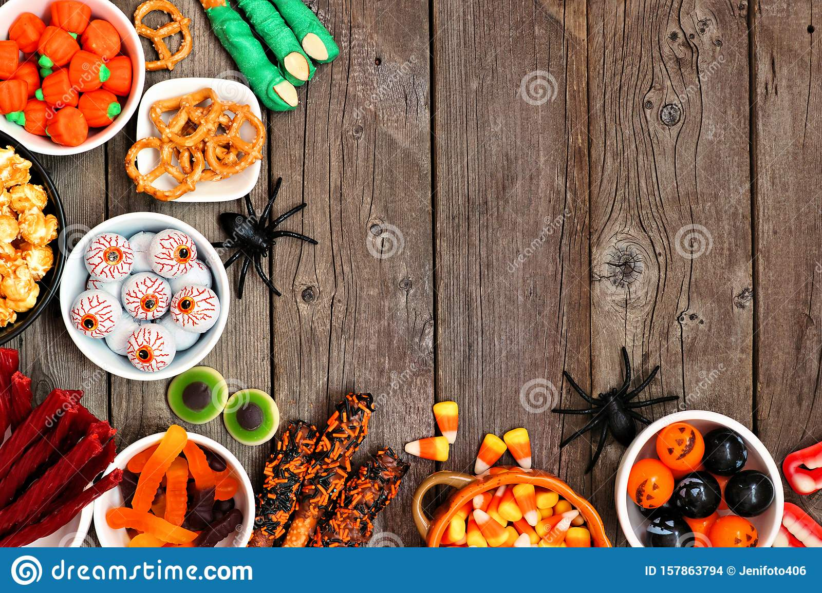 Halloween candy buffet table corner border over a rustic wood background with copy space