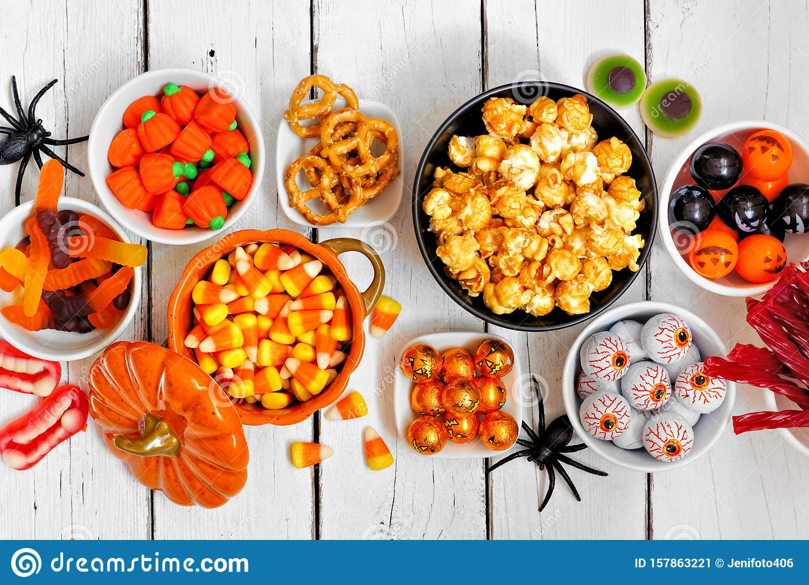 Halloween candy buffet table top view over a white wood background