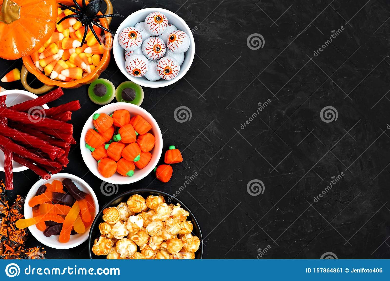 Halloween candy buffet table side border over a black background with copy space