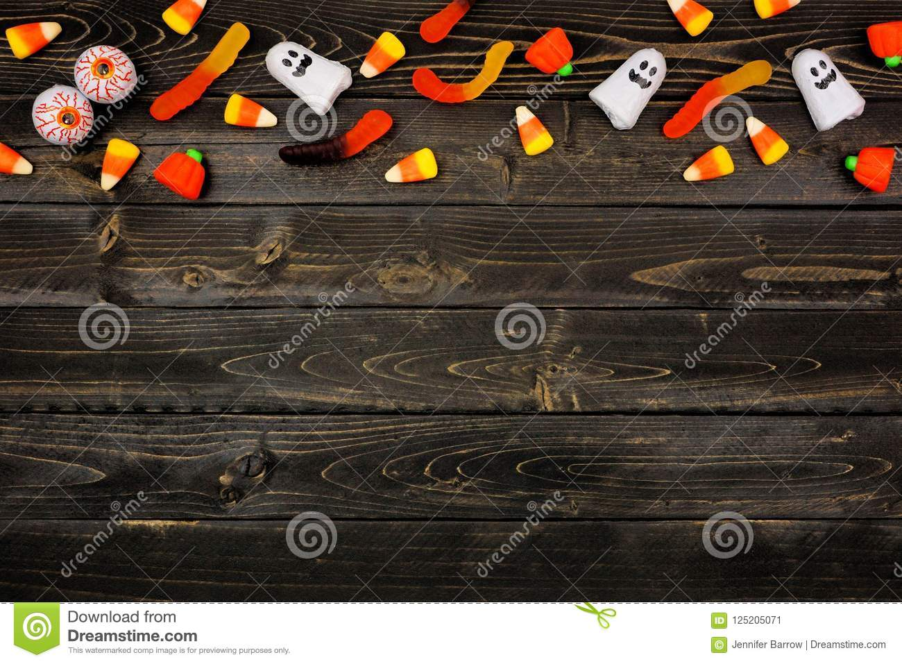 halloween candy top border over dark black wood stock image - image