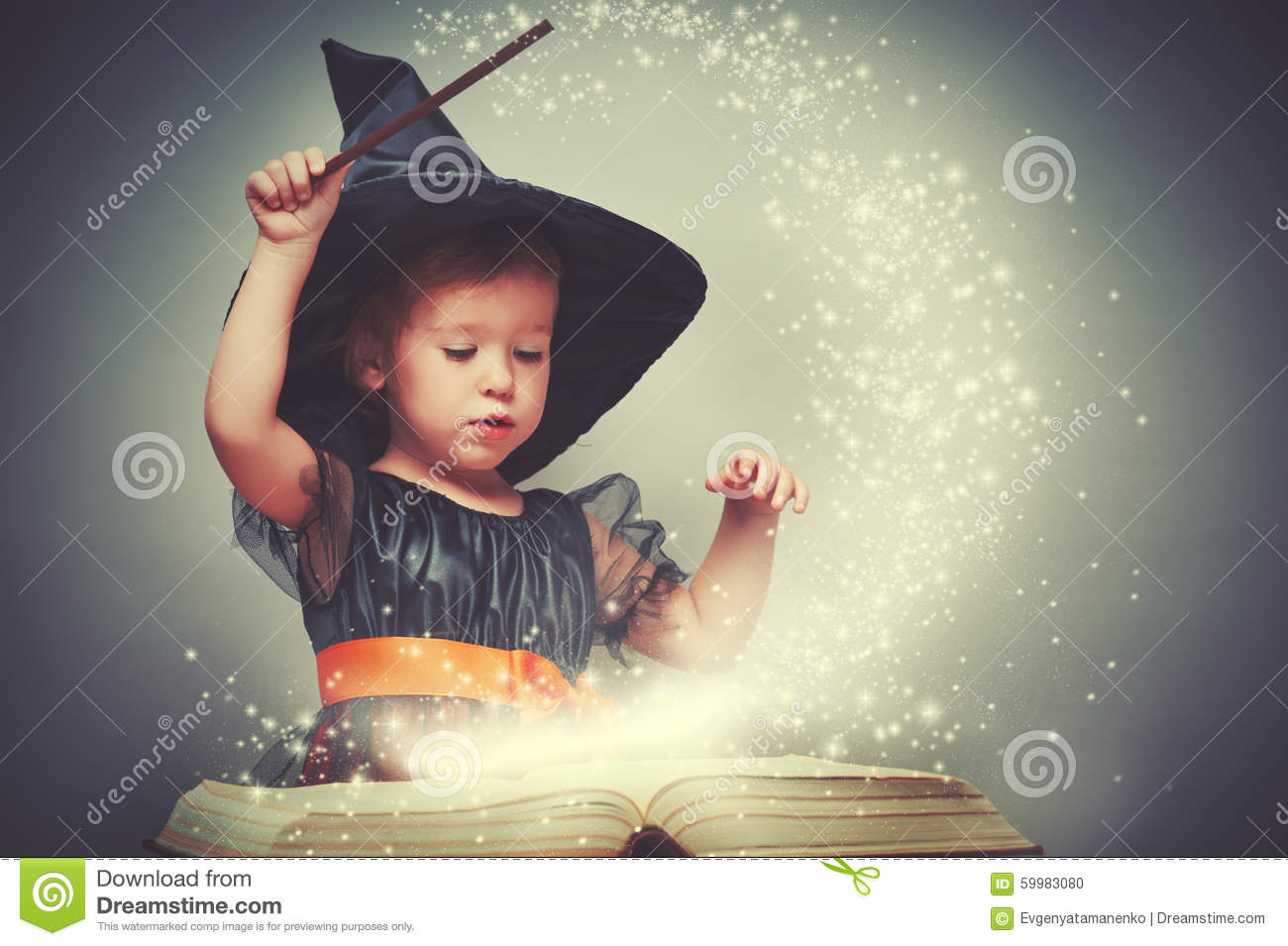 Halloween. cheerful little witch with a magic wand and glowing b