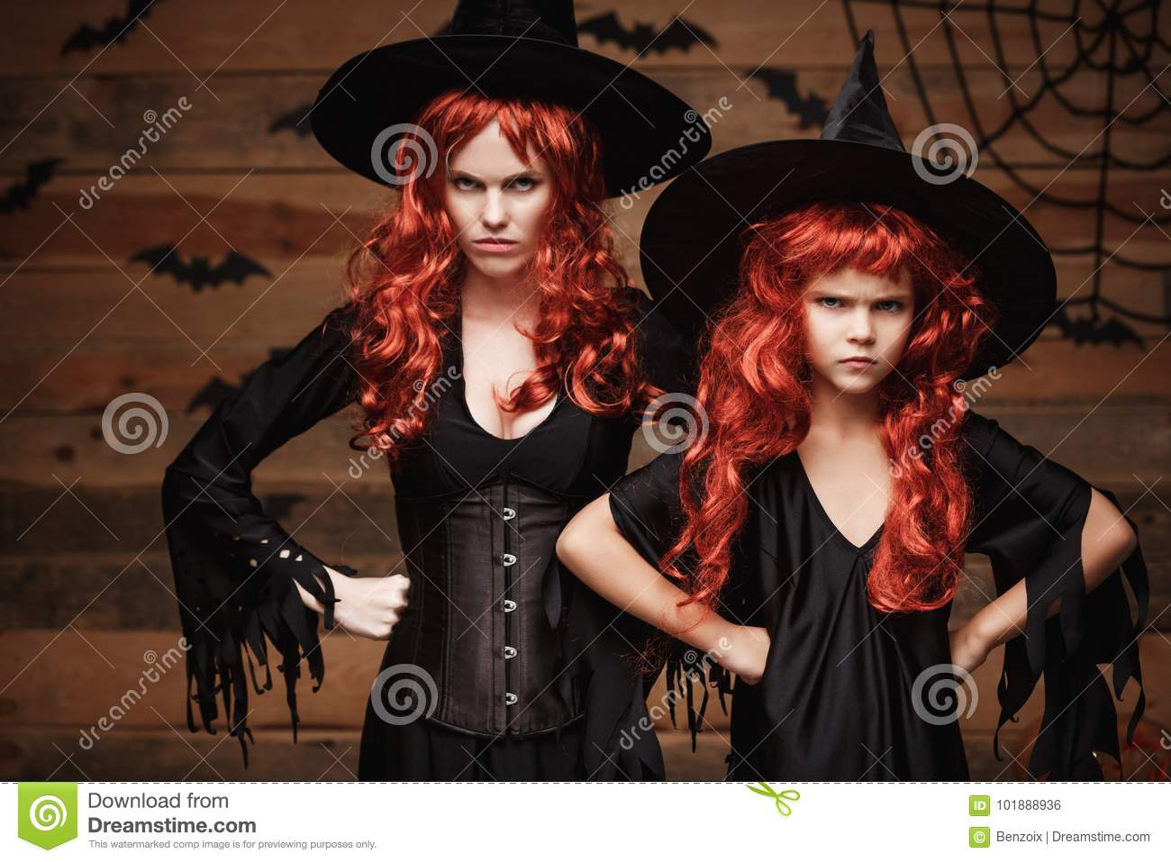 Halloween Concept - Beautiful caucasian mother and her daughter with long red hair in witch costumes with angry fussy facial expre