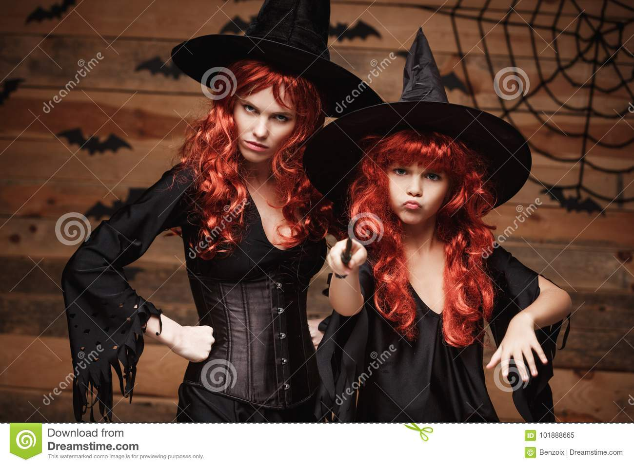 Halloween Concept - Beautiful caucasian mother and her daughter with long red hair in witch costumes and magic wand celebrating Ha