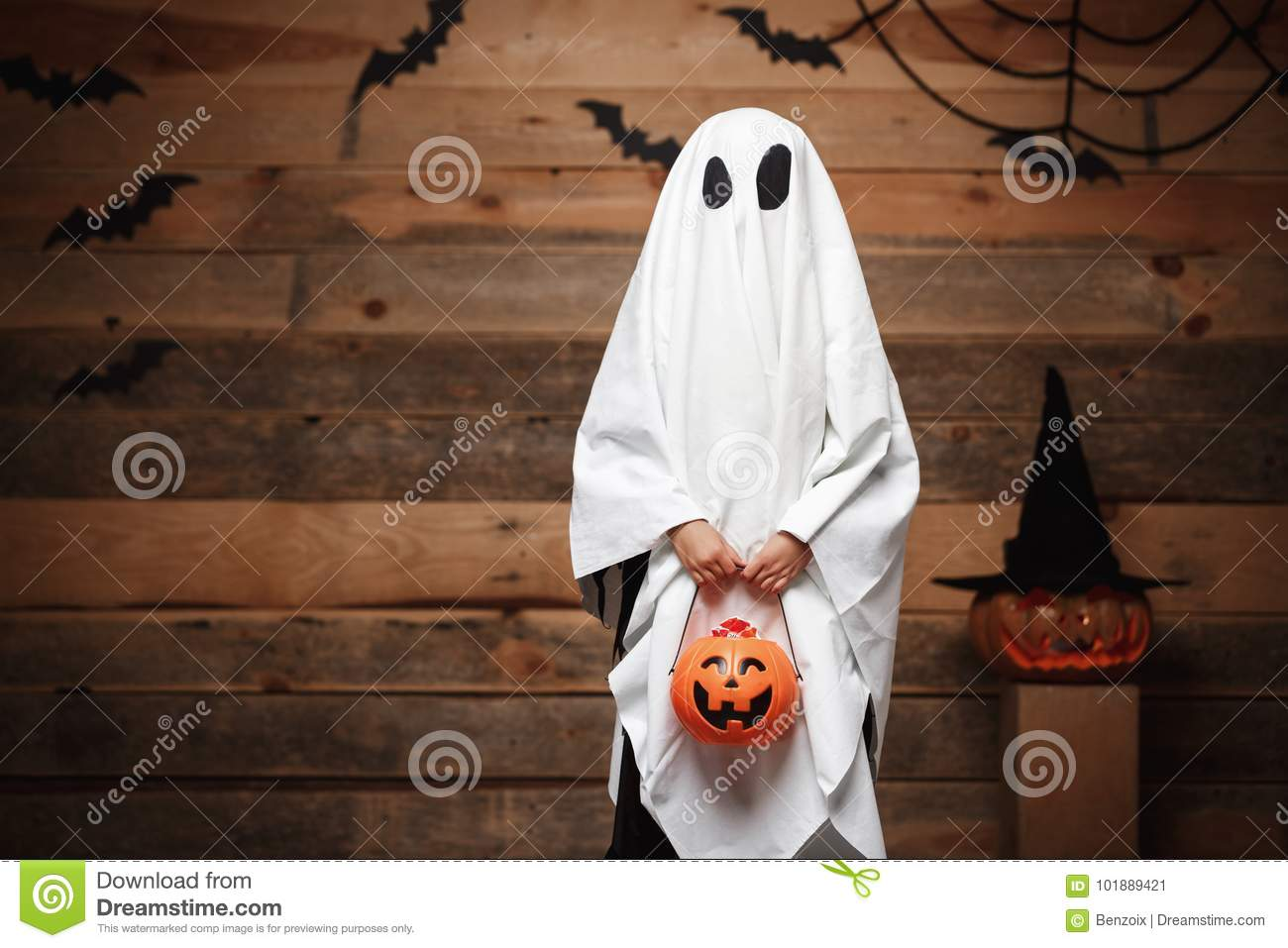 Halloween Concept - little white ghost with halloween pumpkin candy jar doing trick or treat with curved pumpkins over bats and sp