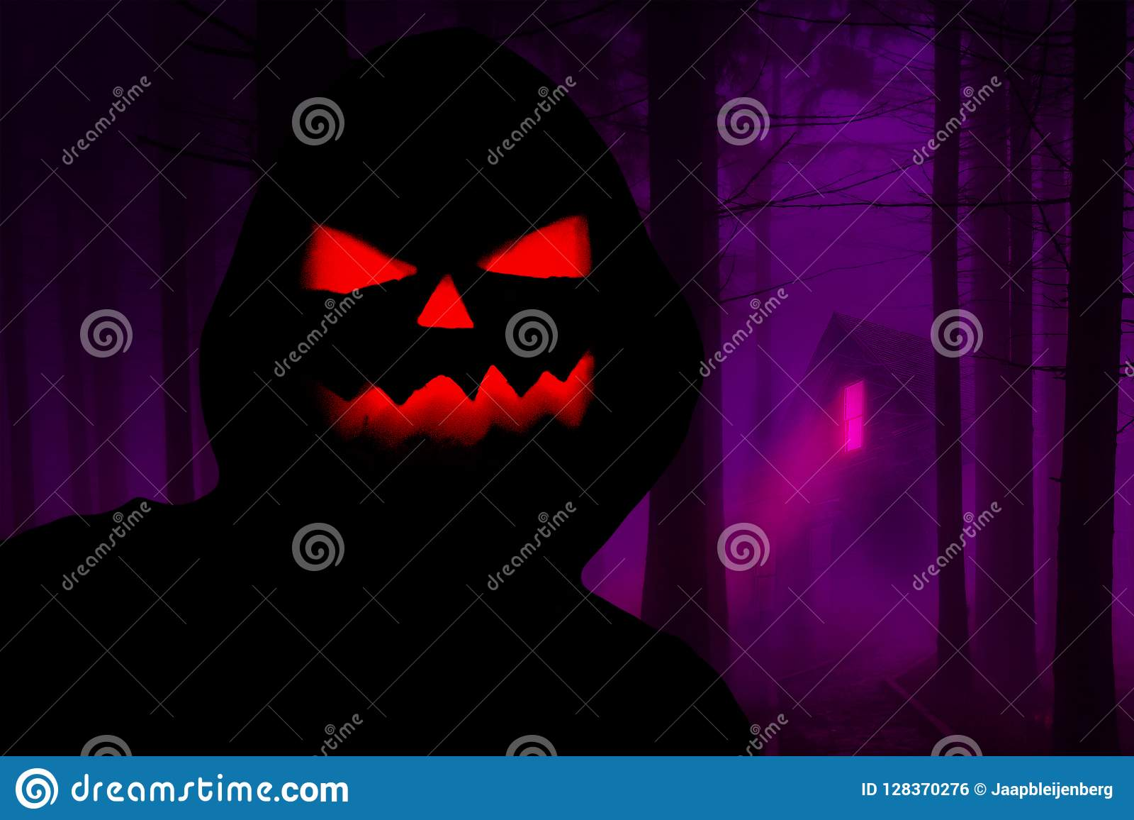 Halloween creepy hooded silhouette with a evil pumpkin face standing in a horror forest with a haunted house in the background
