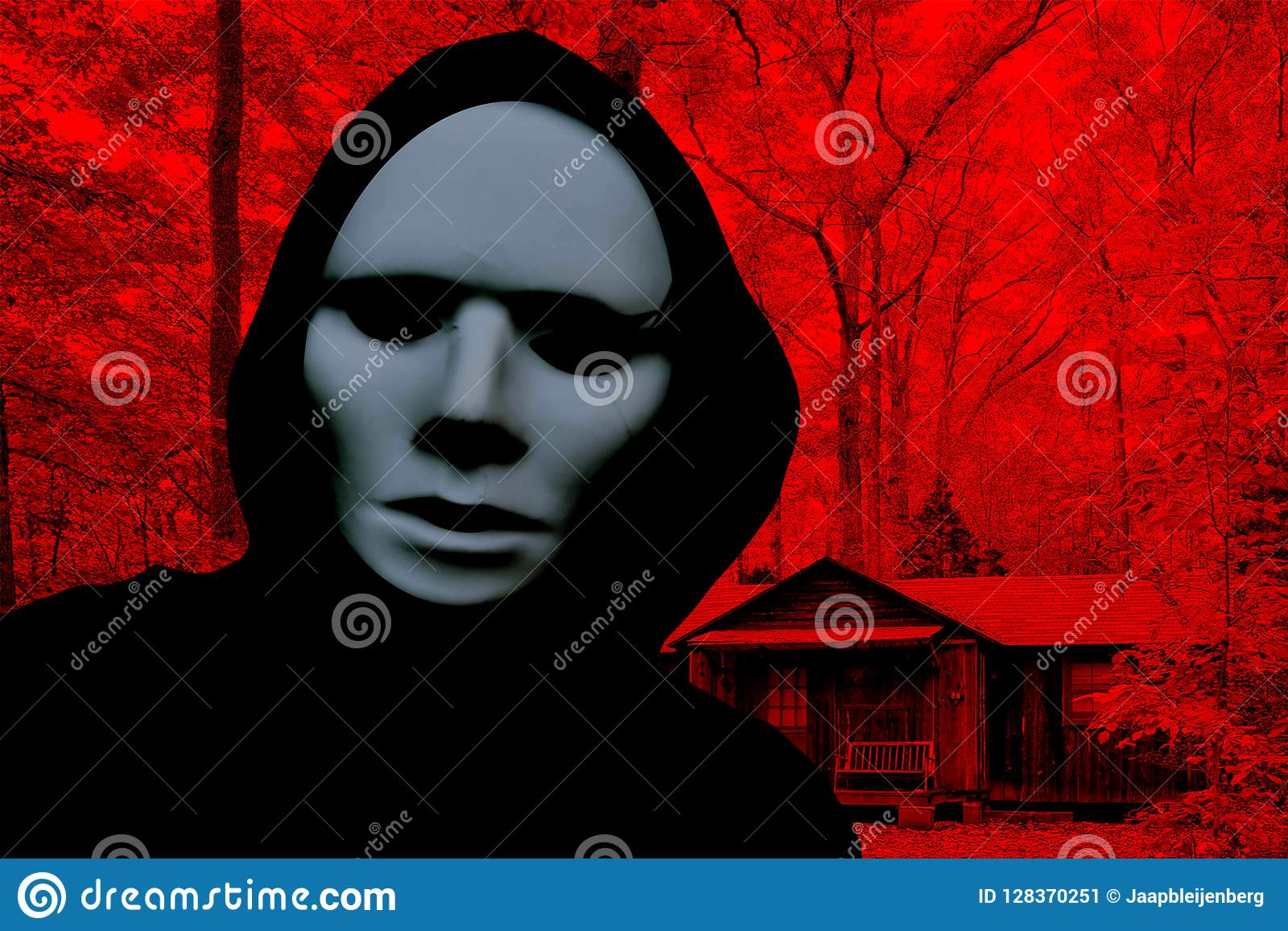 Halloween creepy masked person wearing a hood and standing in front of a cabin in a horror forest