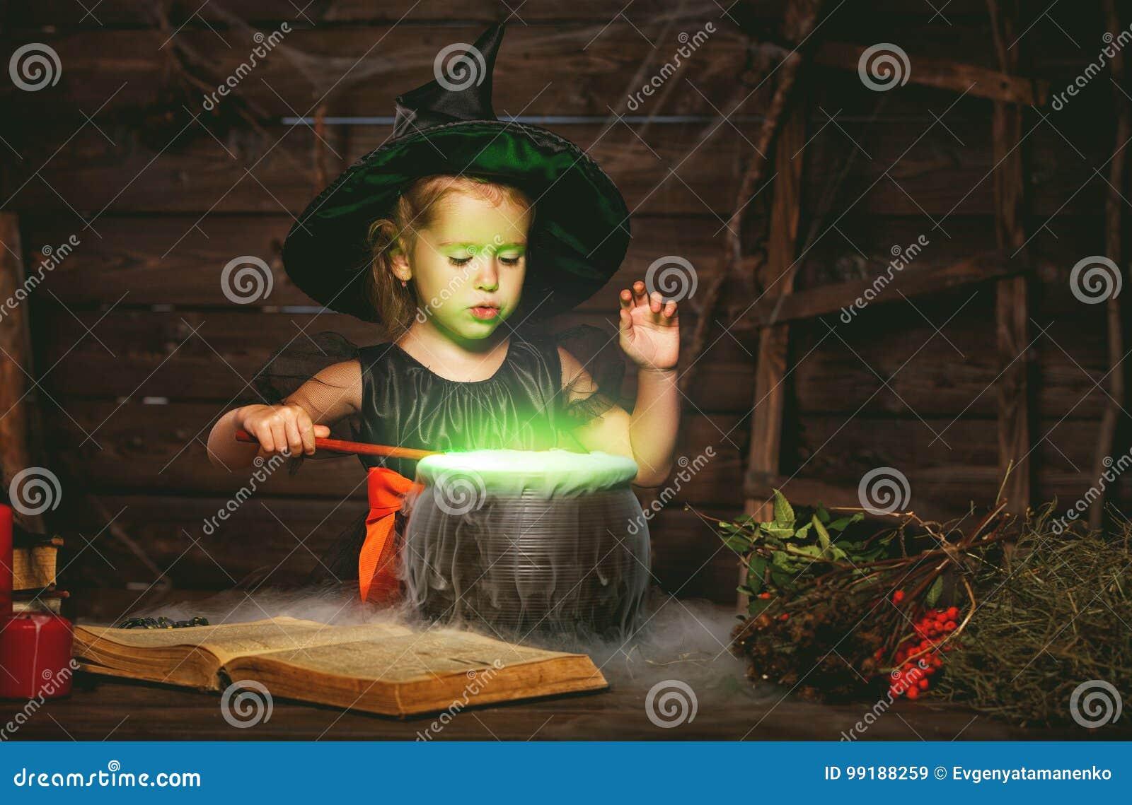 Halloween criança pequena da bruxa que cozinha a poção no caldeirão com