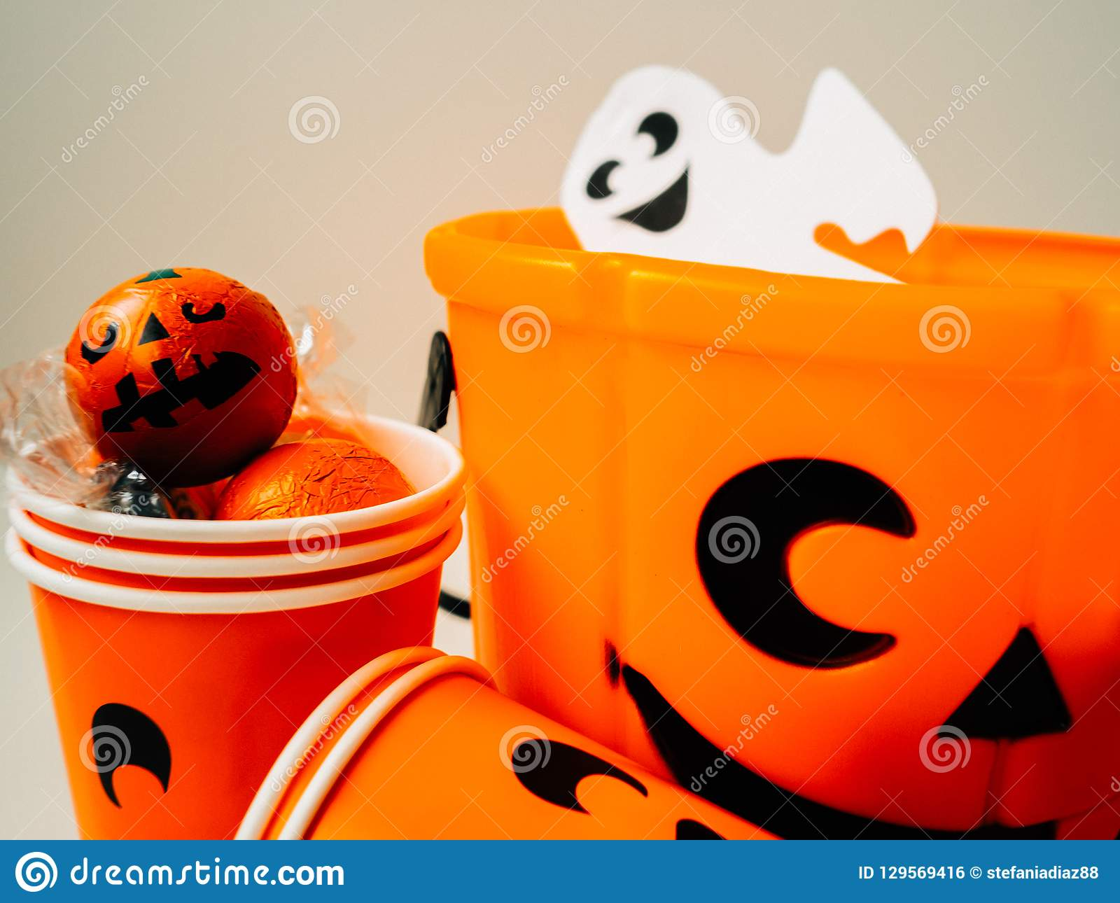 Orange pumpkin filled with chocolates and an orange cardboard cup with happy face and a white ghost