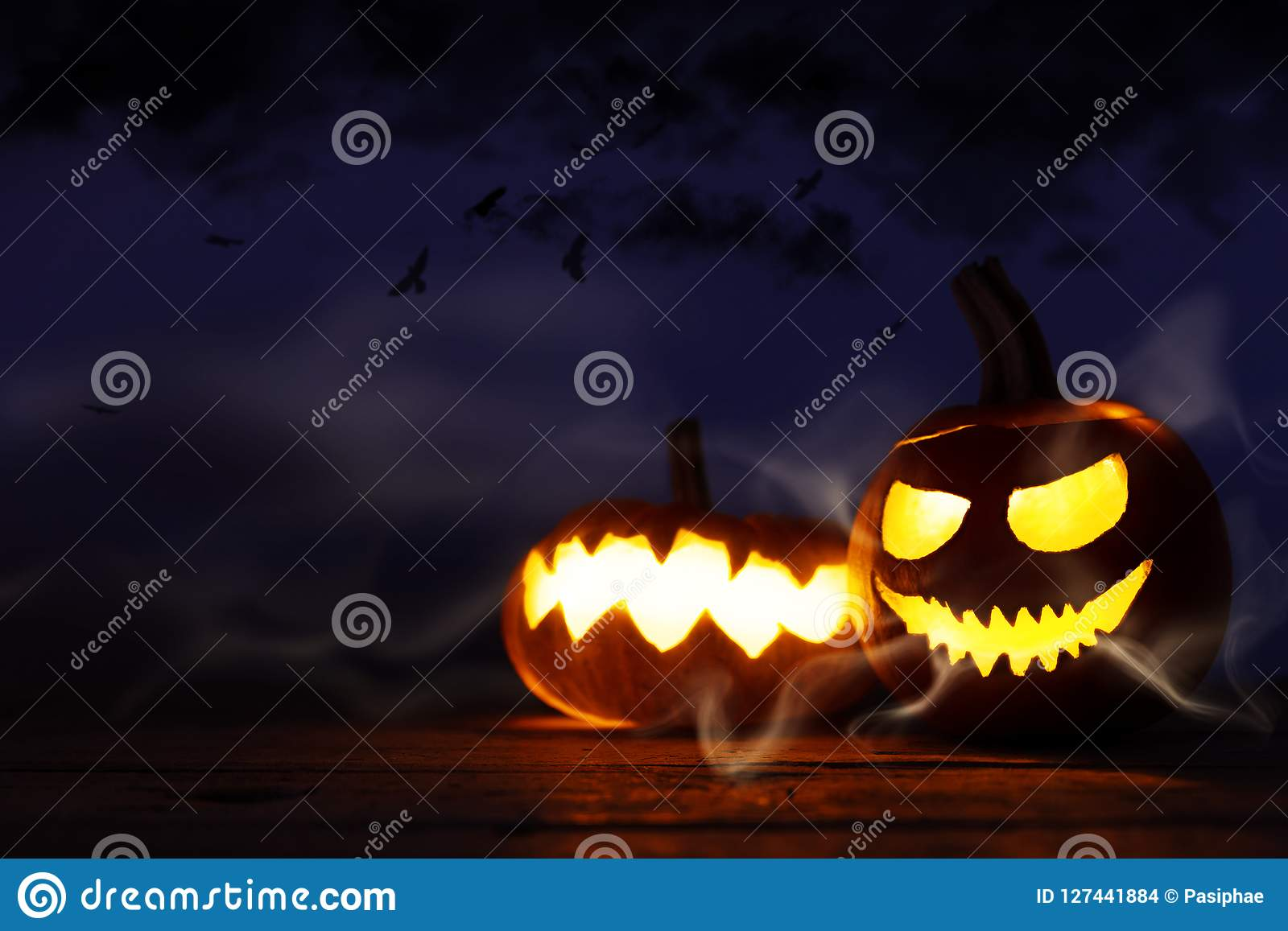 Halloween decoration on wood background, carved pumpkins with sc