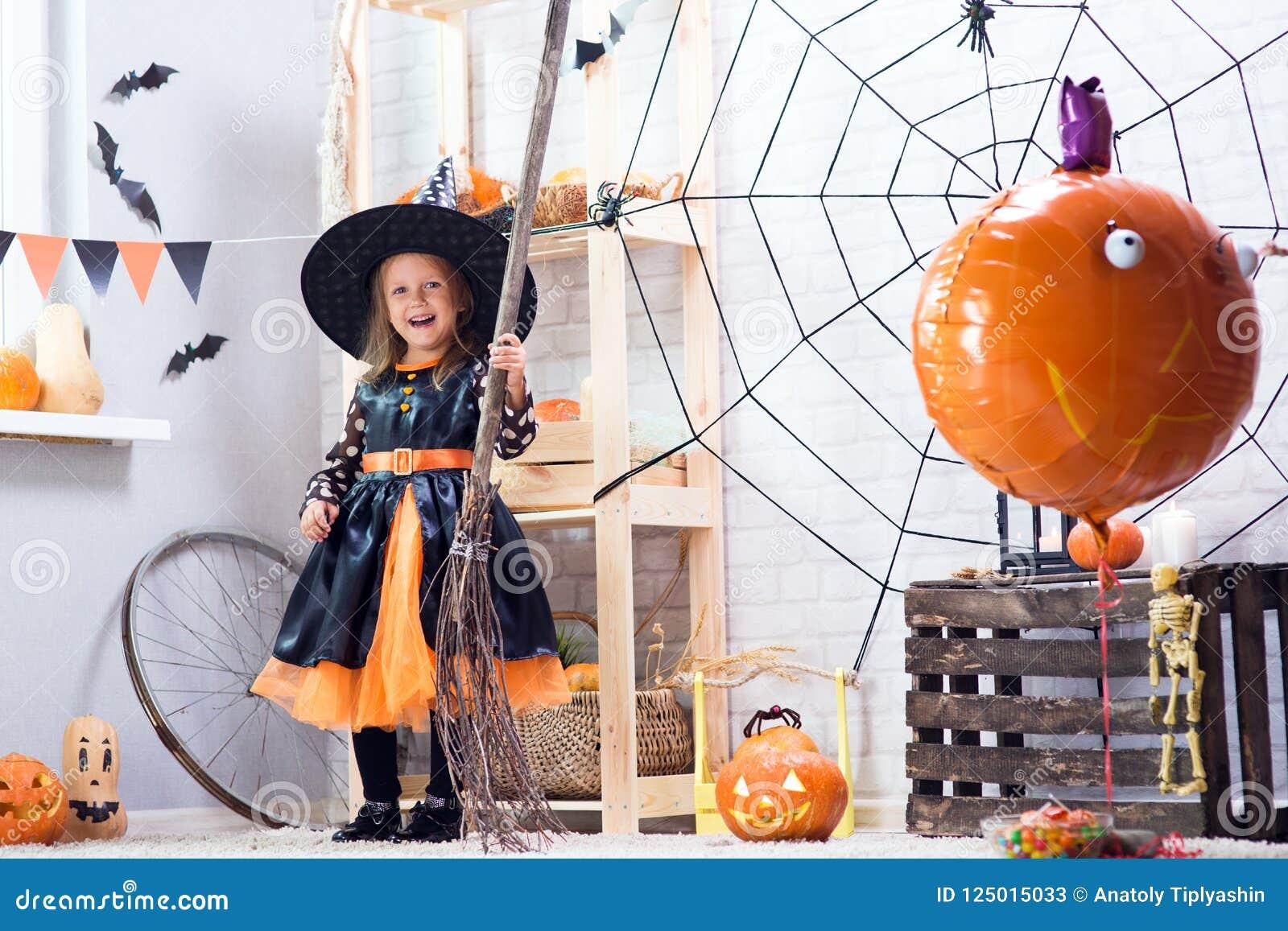 Halloween feliz Uma menina bonita pequena em um cele do traje da bruxa