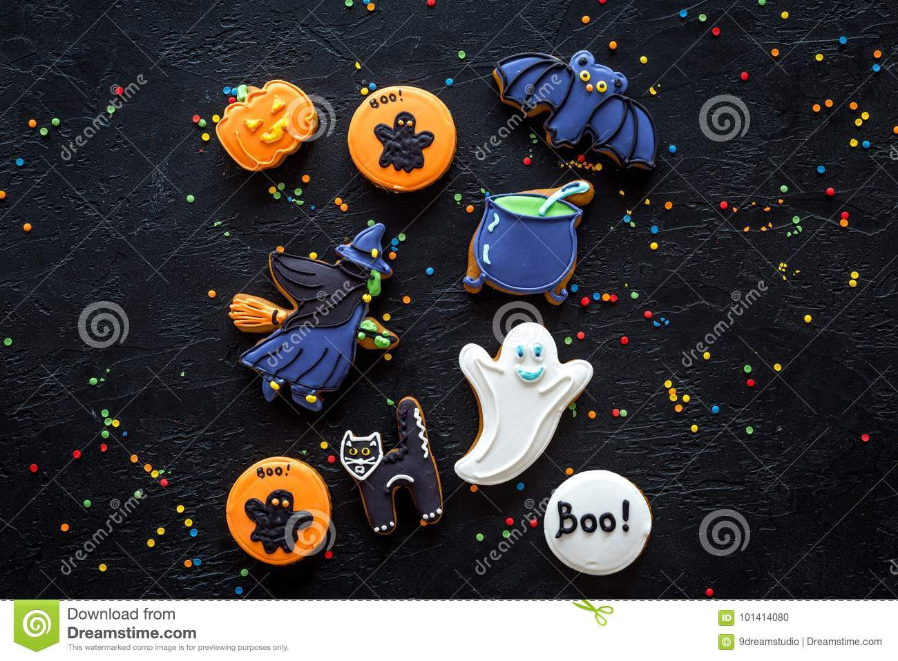 Halloween gingerbread cookies with pictures witch, cauldon and bat on black background top view copyspace