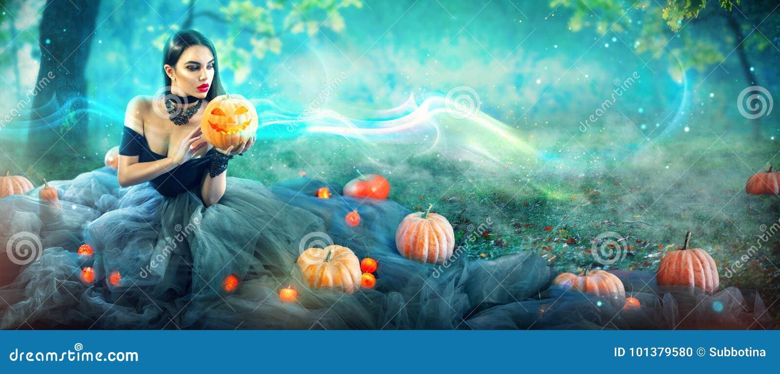 Halloween-heks met een gesneden pompoen en magische lichten in een bos