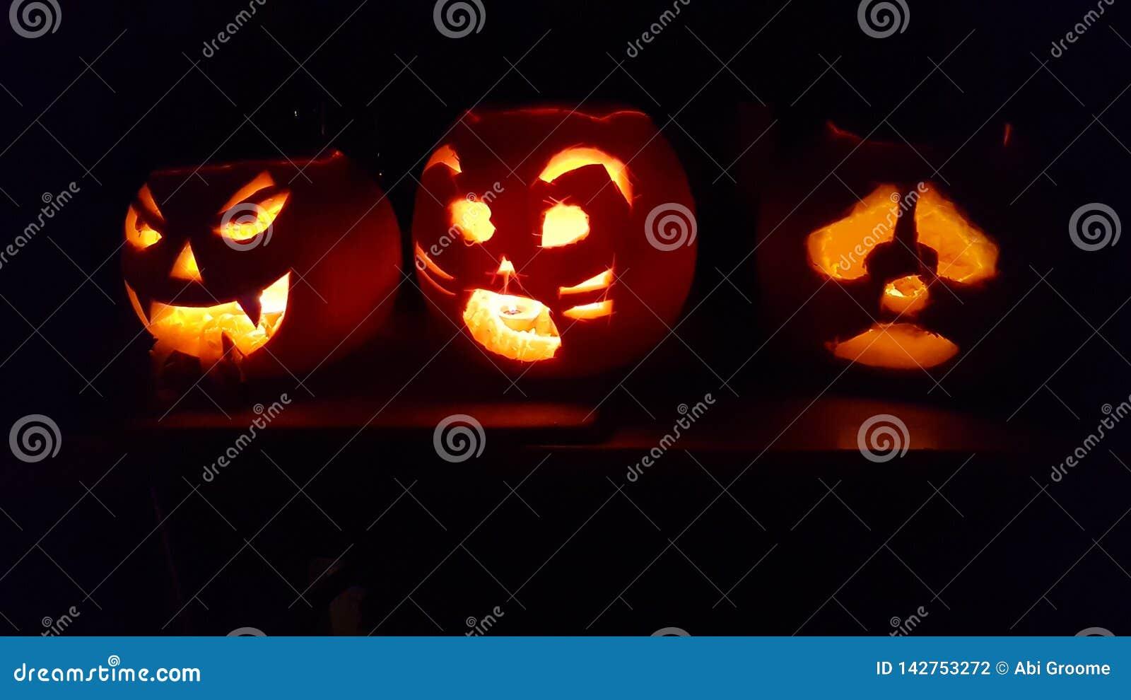 Halloween heureux, une famille des potirons se reposent dans un dessus de cuisine rougeoyant dans l obscurité