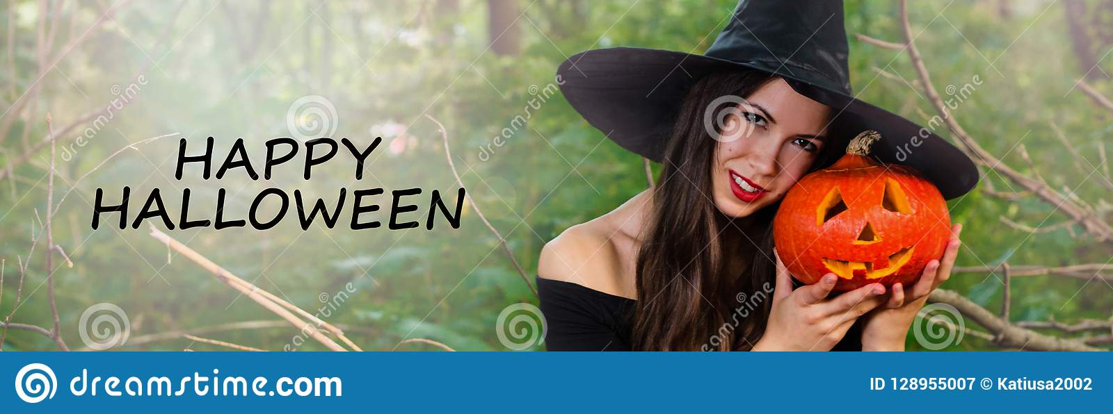 young pretty woman in witch`s hat holding halloween pumpkin jack