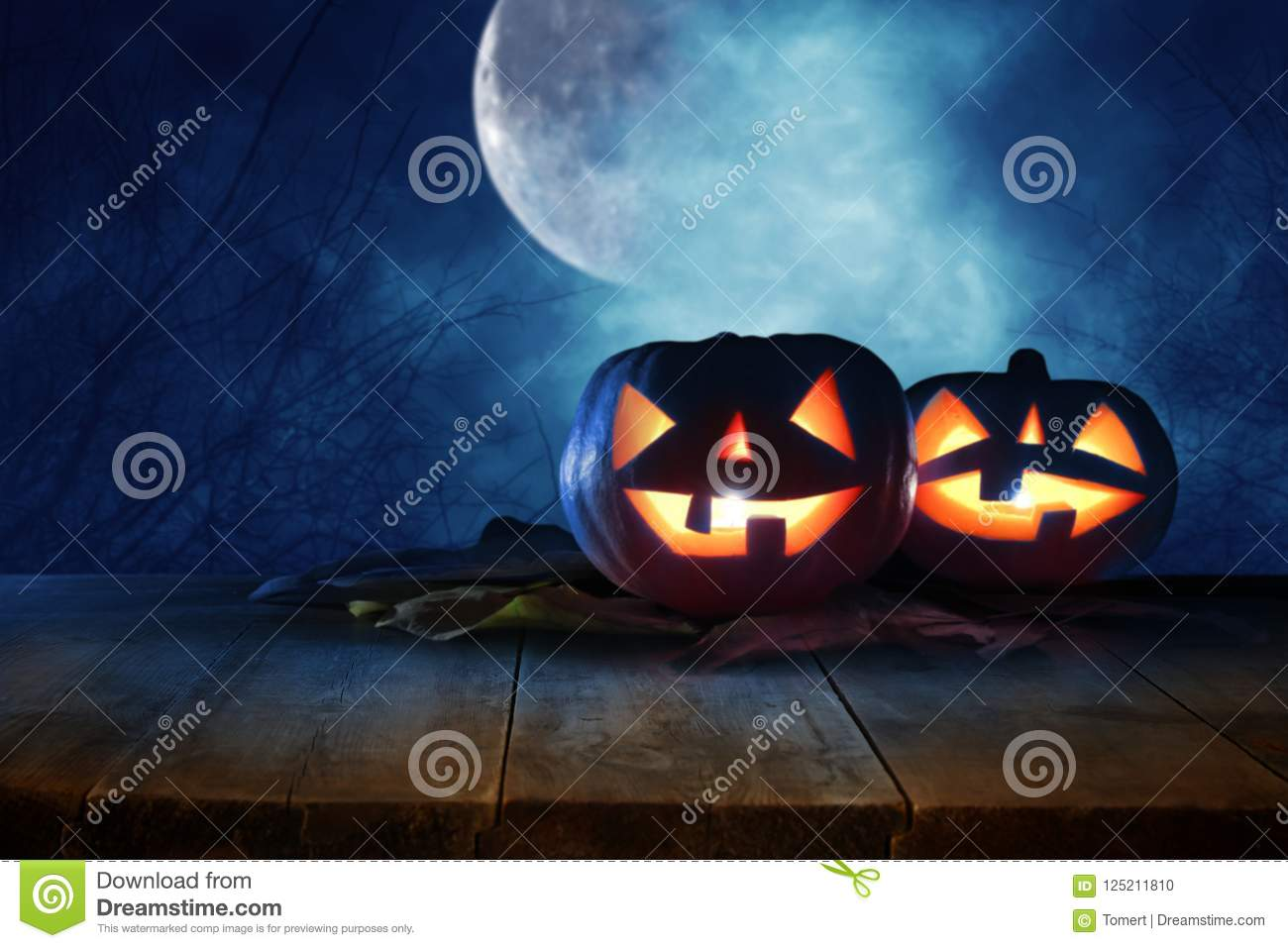 Halloween holiday concept. Empty rustic table in front of Pumpkins over wooden table at night scary, haunted and misty forest. Rea