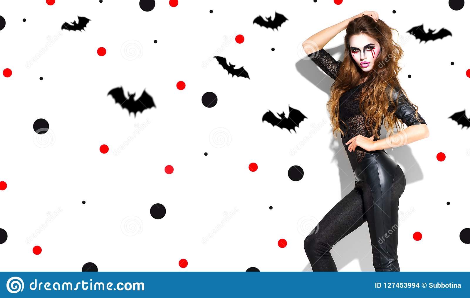 Halloween. Holiday party girl. Beautiful young woman with bright vampire makeup and long hair posing in witches costume
