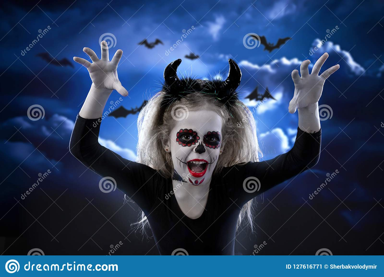 Halloween, holidays, masquerade concept - the portrait of young little beautiful girl with skull makeup on sky night background. H