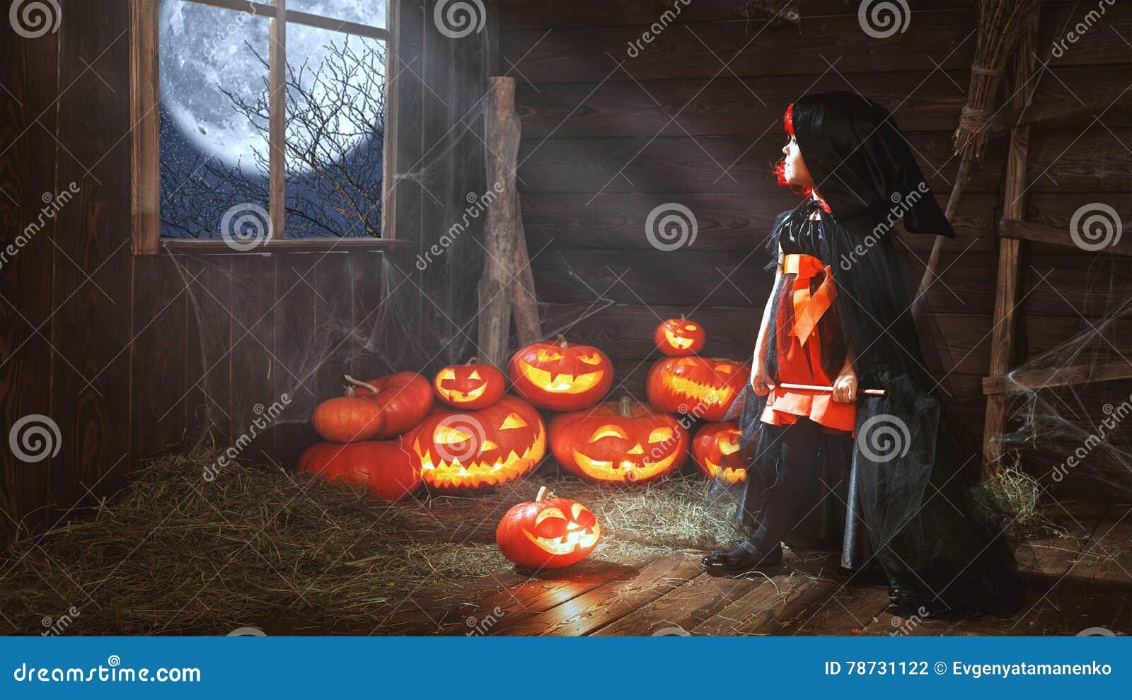 Halloween liten häxa för barn med pumpa vid fönsterwaitinen