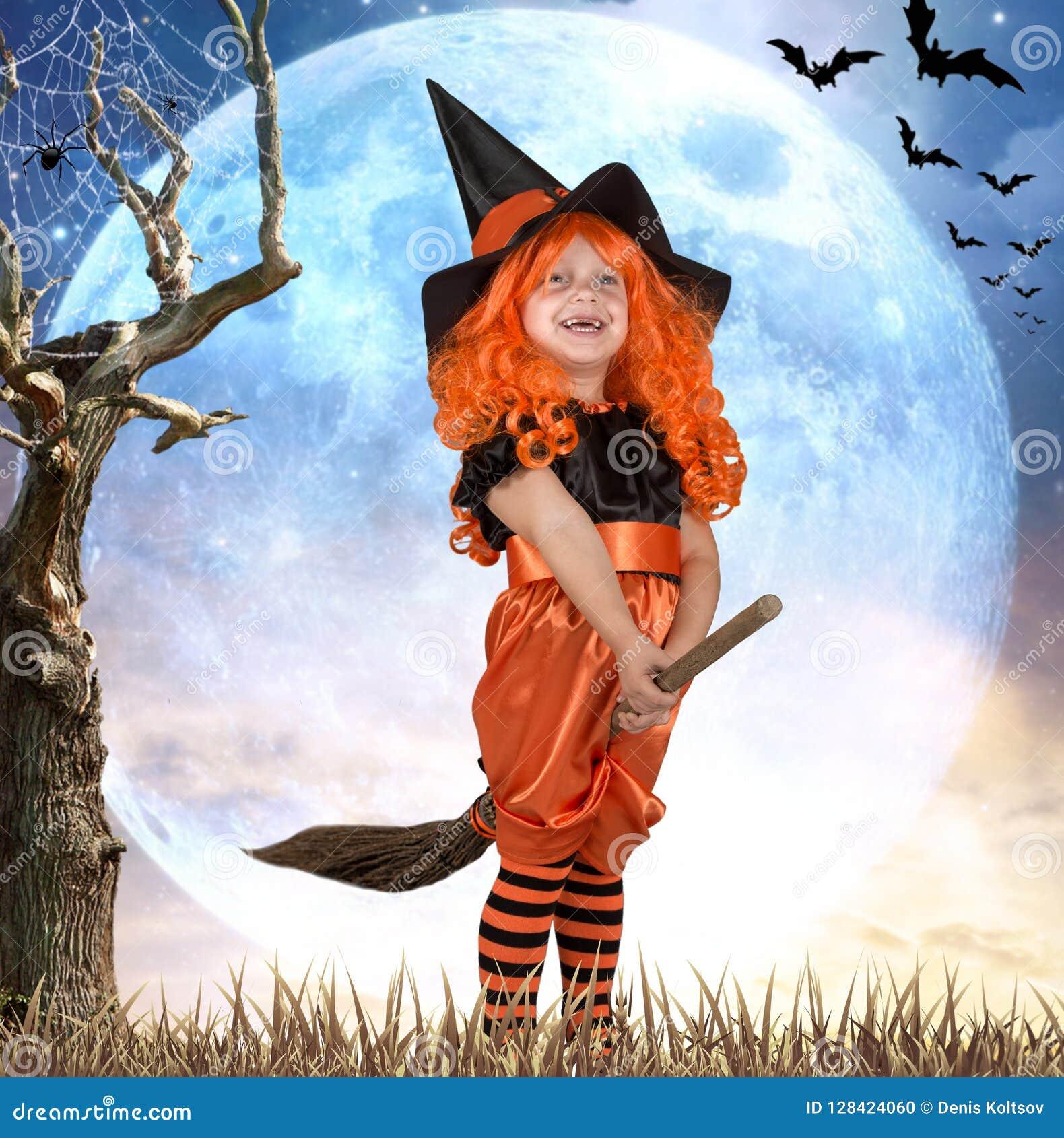 Halloween Mała dziewczynka w kostiumowym czarownicy lataniu na miotle przez niebo