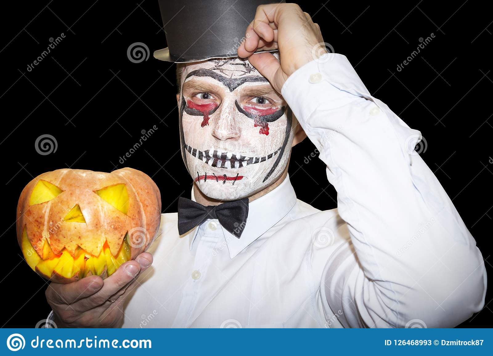 Halloween Maan.Halloween Man With Makeup Holds Yellow Pumpkin On Black