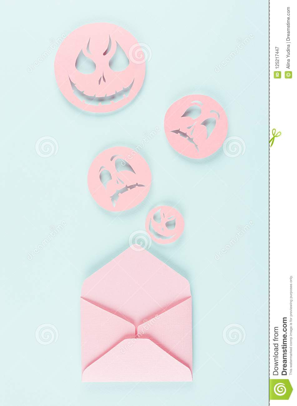 Halloween mock up with open envelope and spooky faces emoji as message of cut paper on pastel trendy mint background.