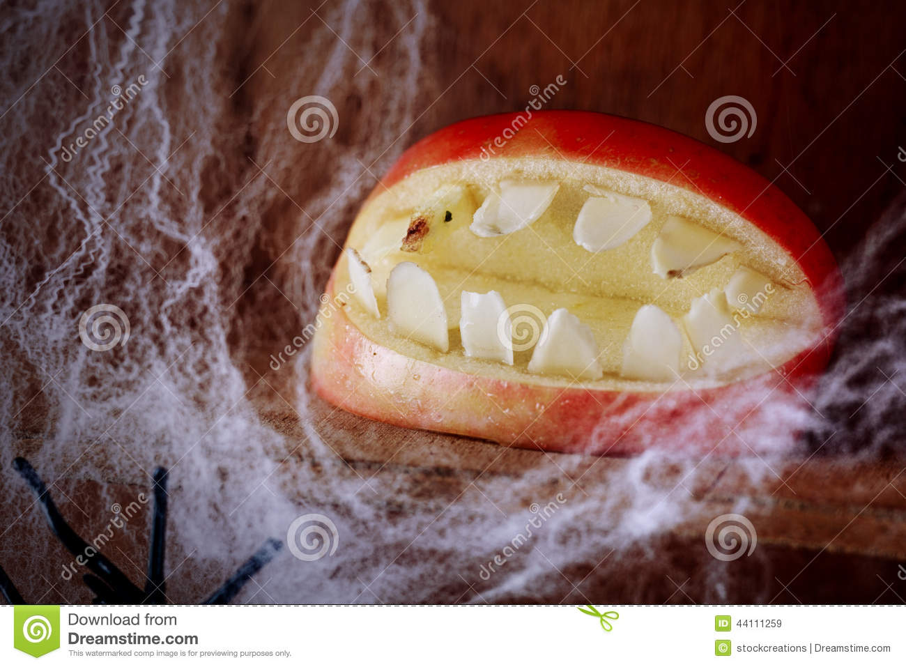ghoulish gaping halloween mouth with teeth made from an apple on a wooden shelf festooned with spider webs in a scary festive background for allhallows eve