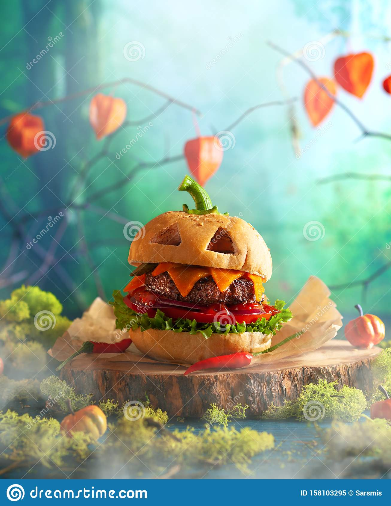 Halloween party burger in shape of scary pumpkin on natural wooden board. Halloween food concept