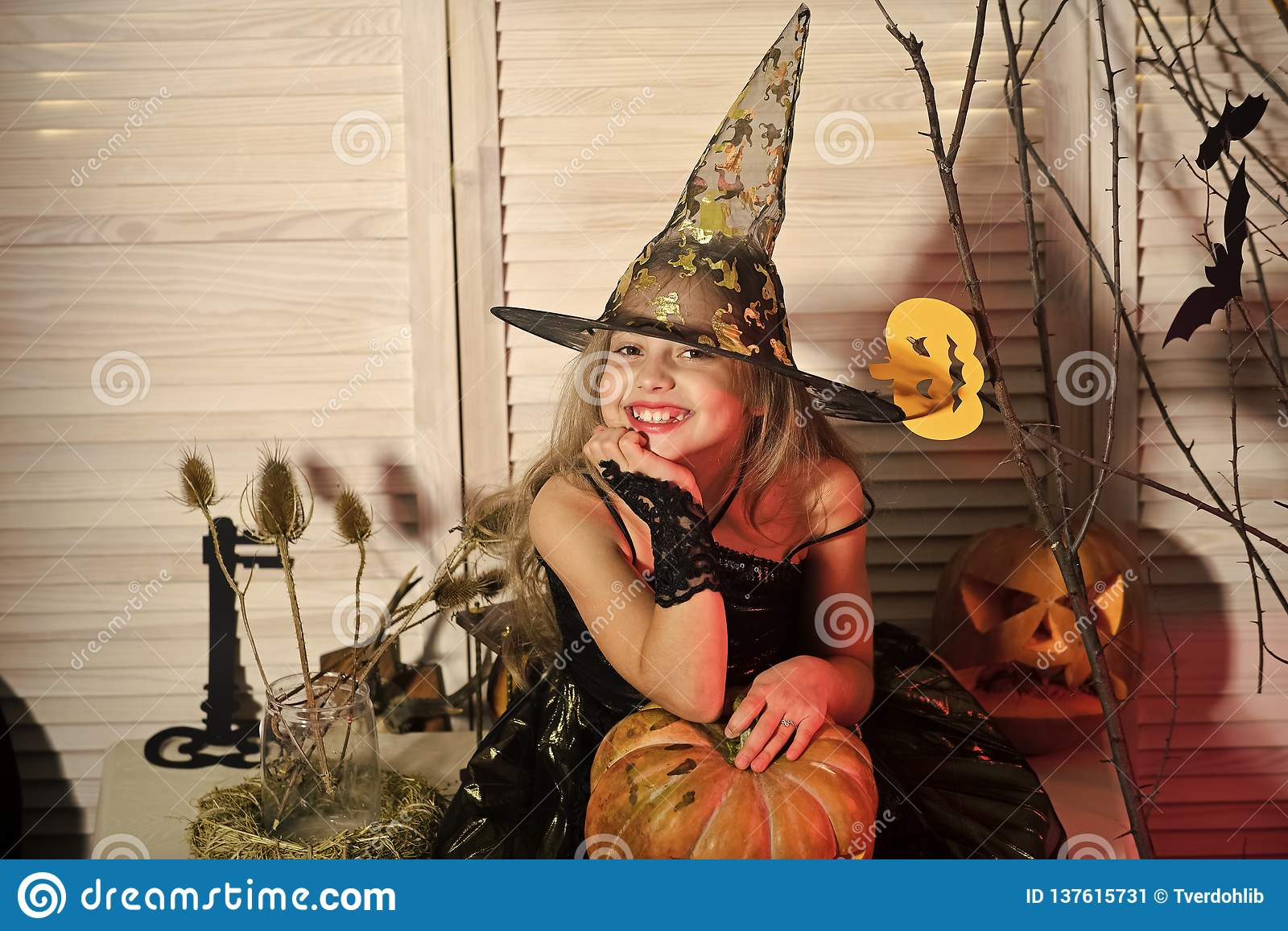 Halloween party and celebration concept. Little witch with Halloween decor