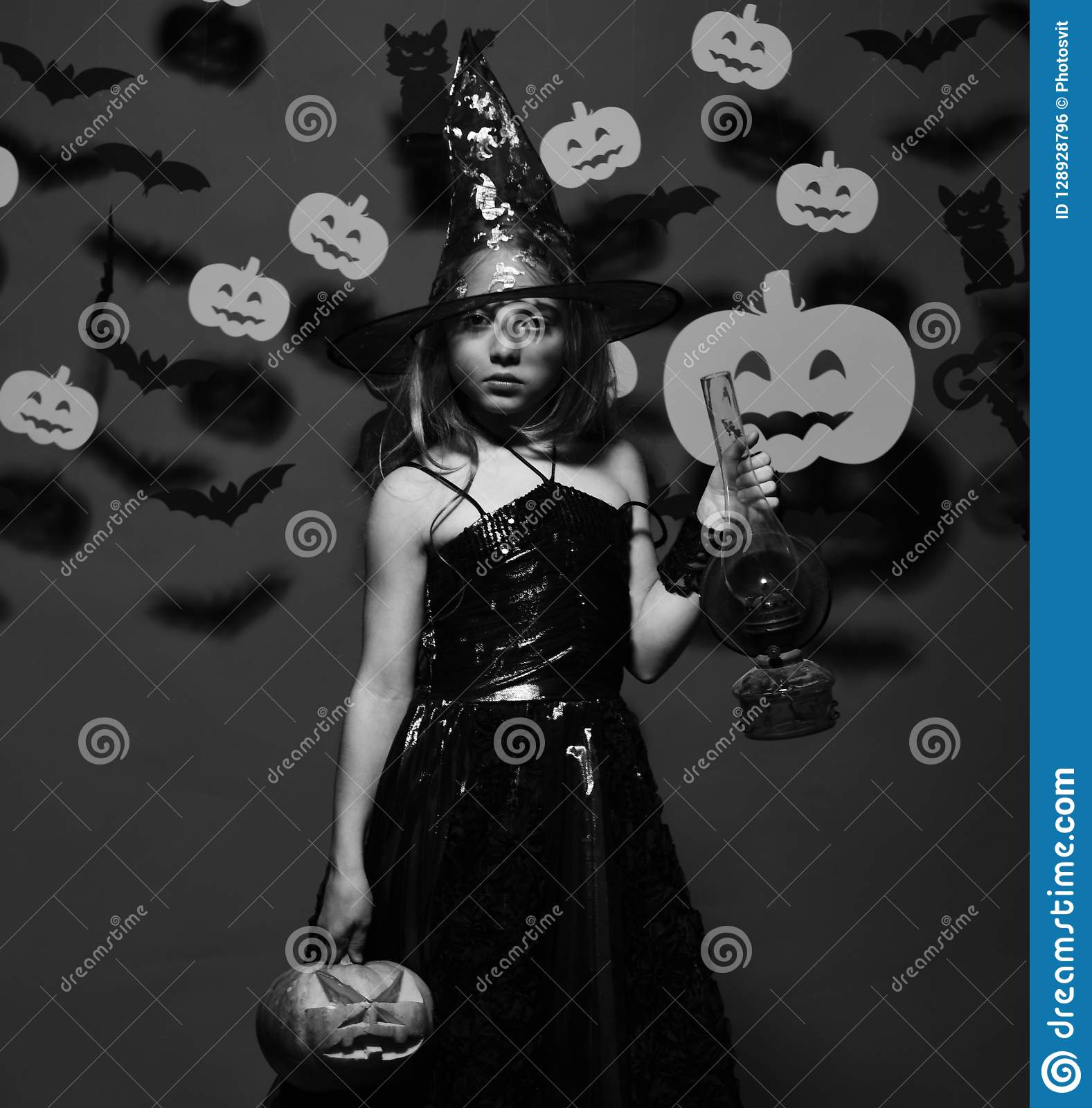 Halloween party and decorations concept. Kid in spooky witches costume
