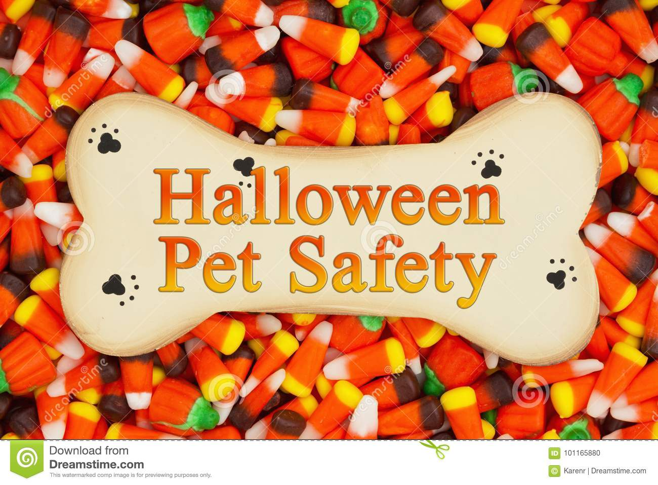 halloween pet safety message on wood dog bone with candy corn background