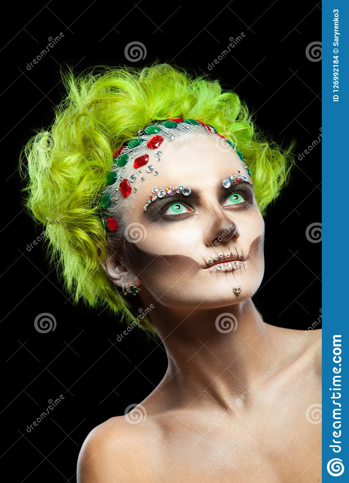 Halloween. Portrait of young beautiful girl with make-up skeleton on her face. And green hair. Isolated on black