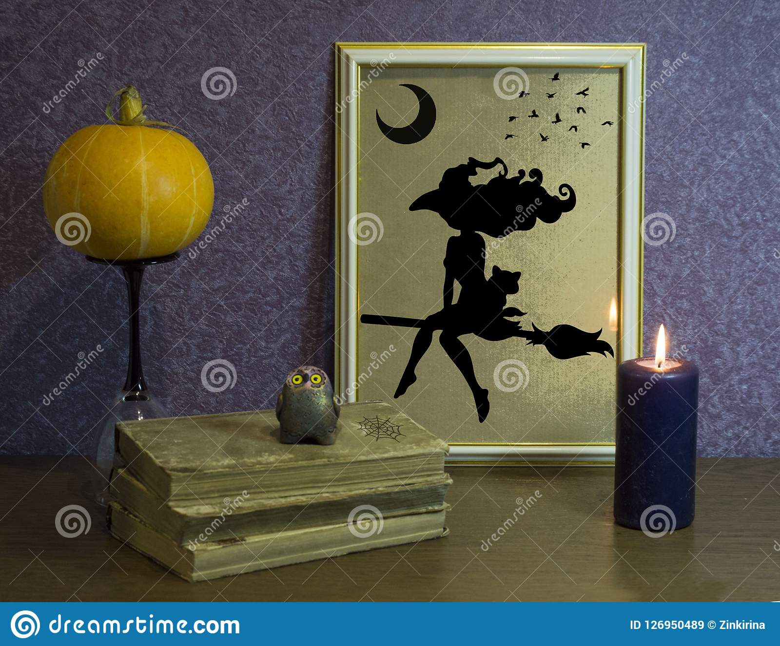 Halloween pumpkin. The book of arcane magic. Frame and burning candle.