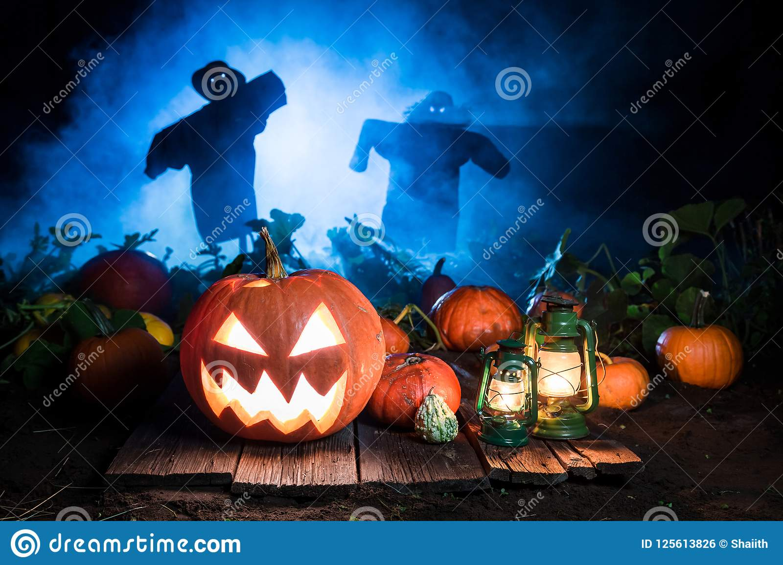 Halloween pumpkin with scarecrows and blue mist