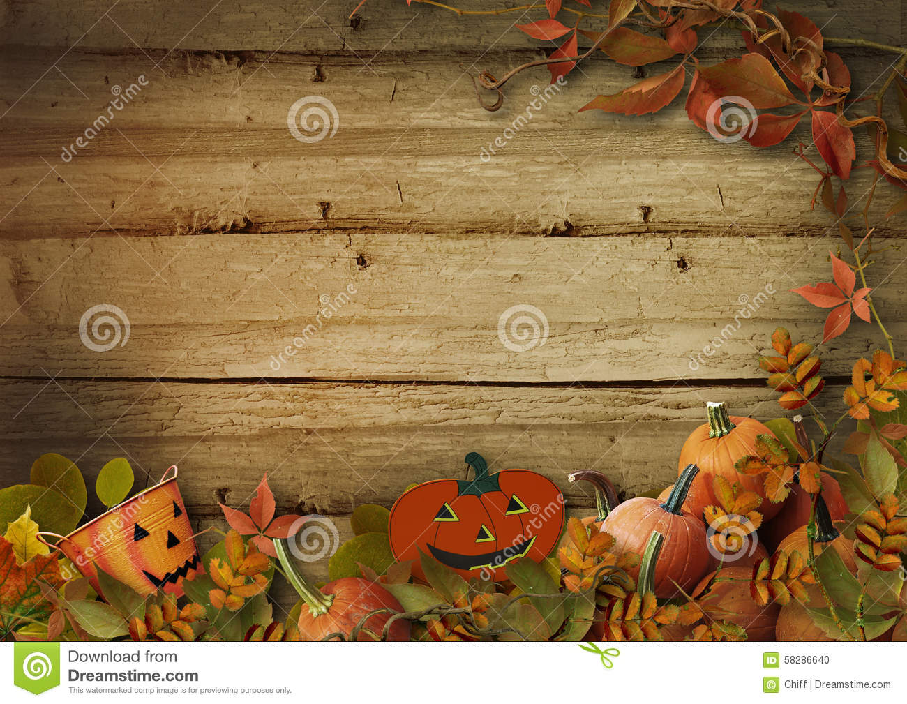 halloween pumpkins and autumn leaves on wooden background