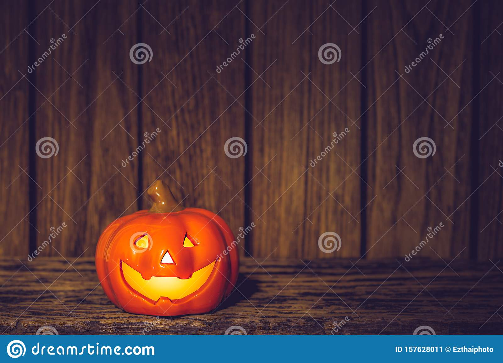 Halloween Pumpkins jack o lanterns with funny faces on grunge wood at night. Halloween background with copy space for your