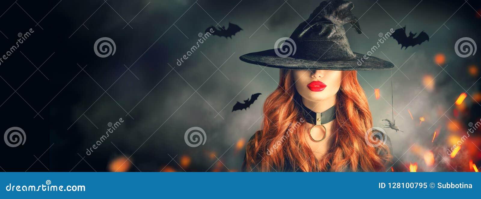 Halloween Retrato  sexy  da bruxa Jovem mulher bonita no chapéu das bruxas com cabelo vermelho encaracolado longo sobre a florest