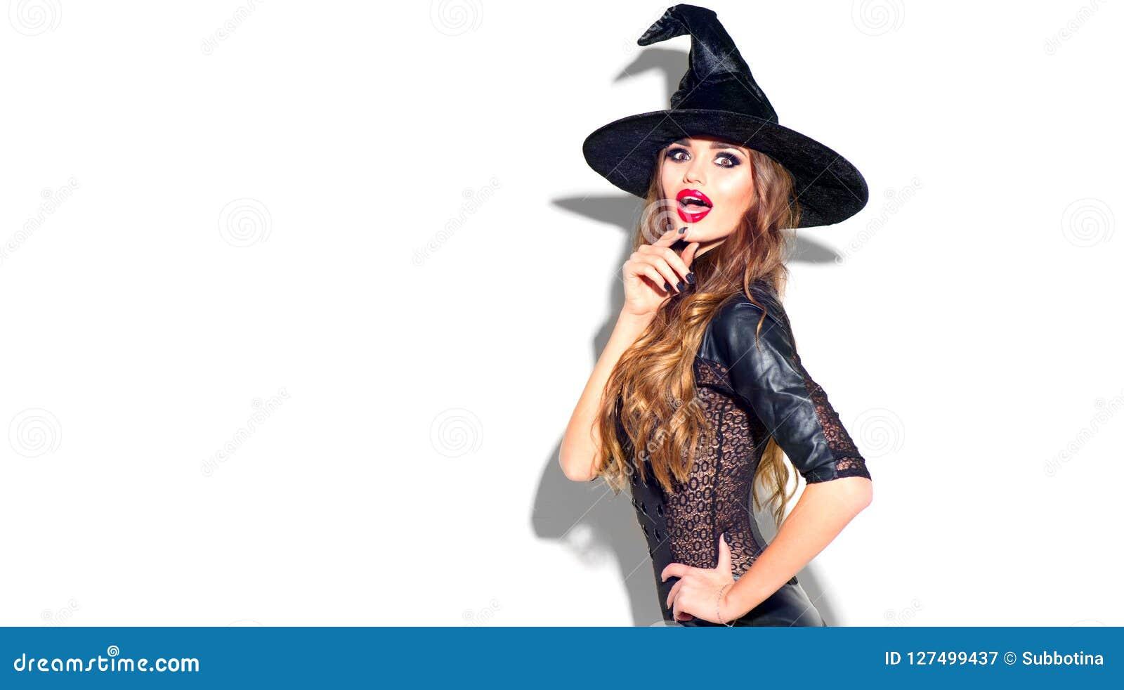Halloween Sexig häxa med ljus feriemakeup Härlig förvånad ung kvinna som poserar i sexig dräkt för häxor