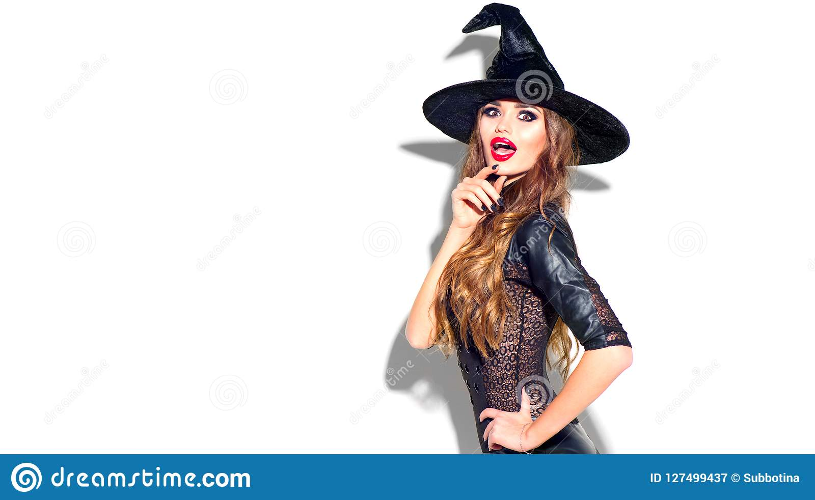 Halloween Sexy Hexe mit hellem Feiertagsmake-up Schöne überraschte junge Frau, die im sexy Kostüm der Hexen aufwirft