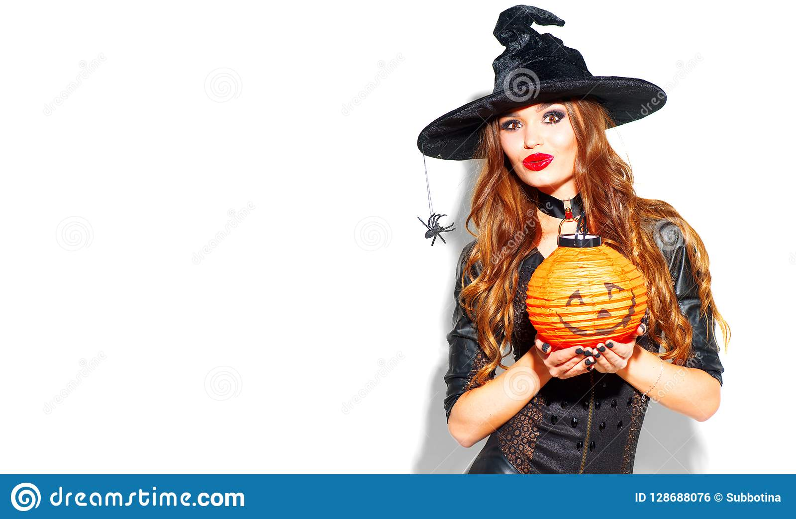 Halloween. witch with bright holiday makeup. Beautiful young woman posing in witches costume with pumpkin lantern