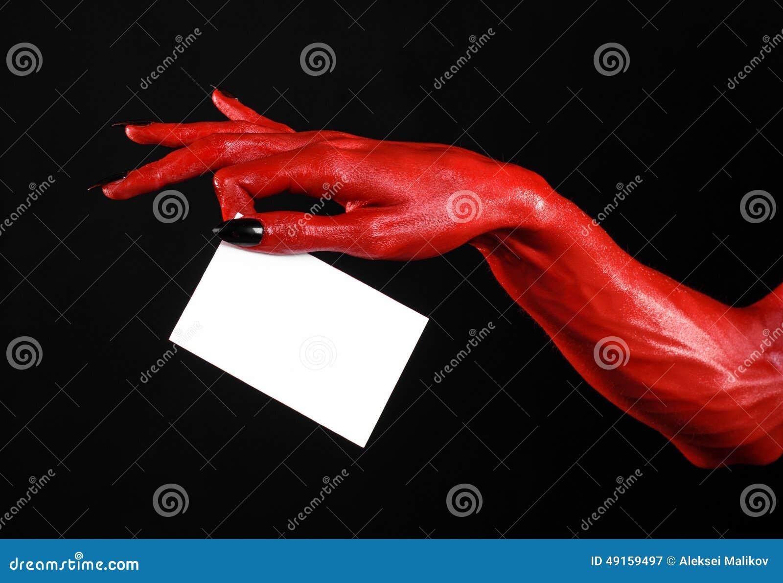 Halloween-thema: Rode duivelshand met zwarte spijkers die een lege witte kaart op een zwarte achtergrond houden