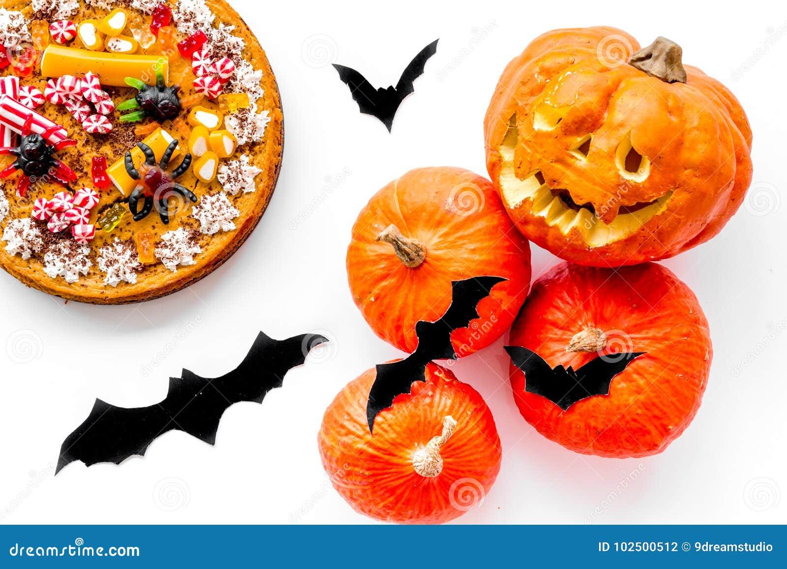 Halloween-Tradition Kürbiskuchen, Kürbis mit geschnitztem Gesicht und Schläger auf Draufsicht des weißen Hintergrundes