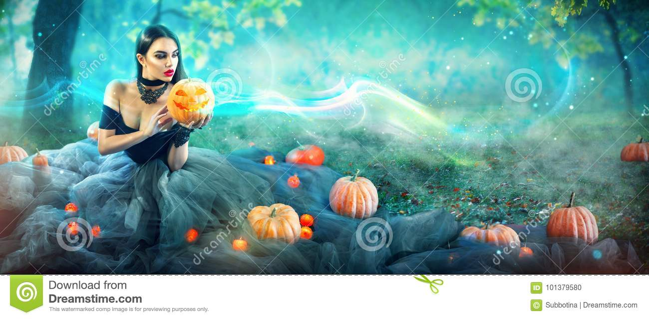 Halloween witch with a carved pumpkin and magic lights in a forest