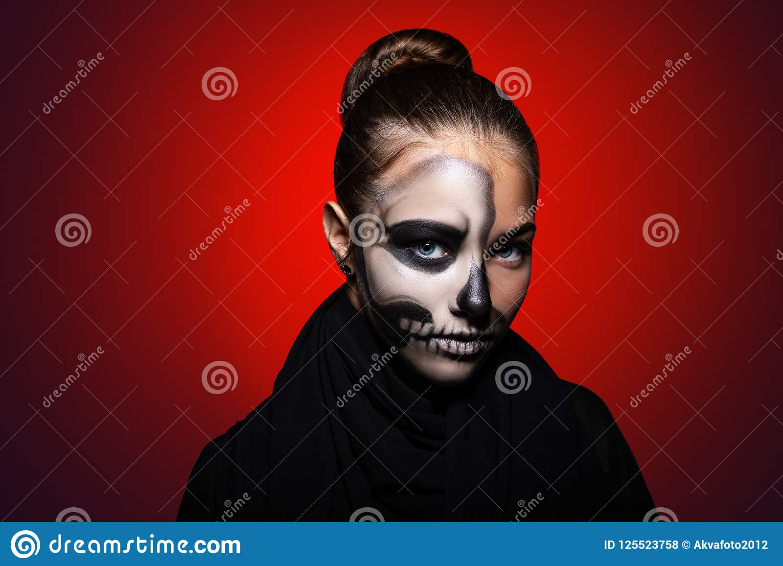 Halloween. young beautiful girl with skeleton makeup on her face. Girl on a bright red background