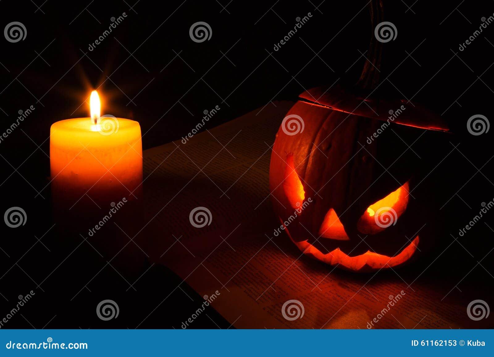 Halloweenowa bania i świeczka na książce