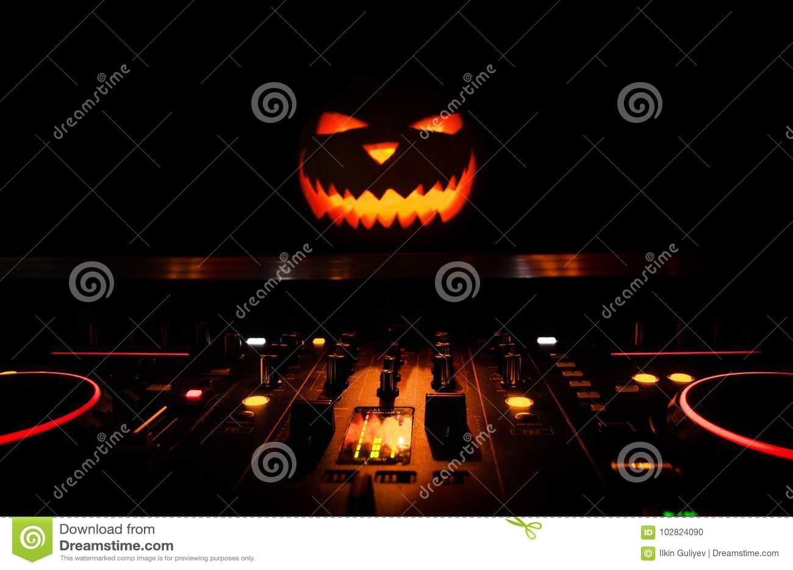Halloweenowa bania na dj stole z hełmofonami na ciemnym tle z kopii przestrzenią Szczęśliwe Halloweenowe festiwal dekoracje, muzy
