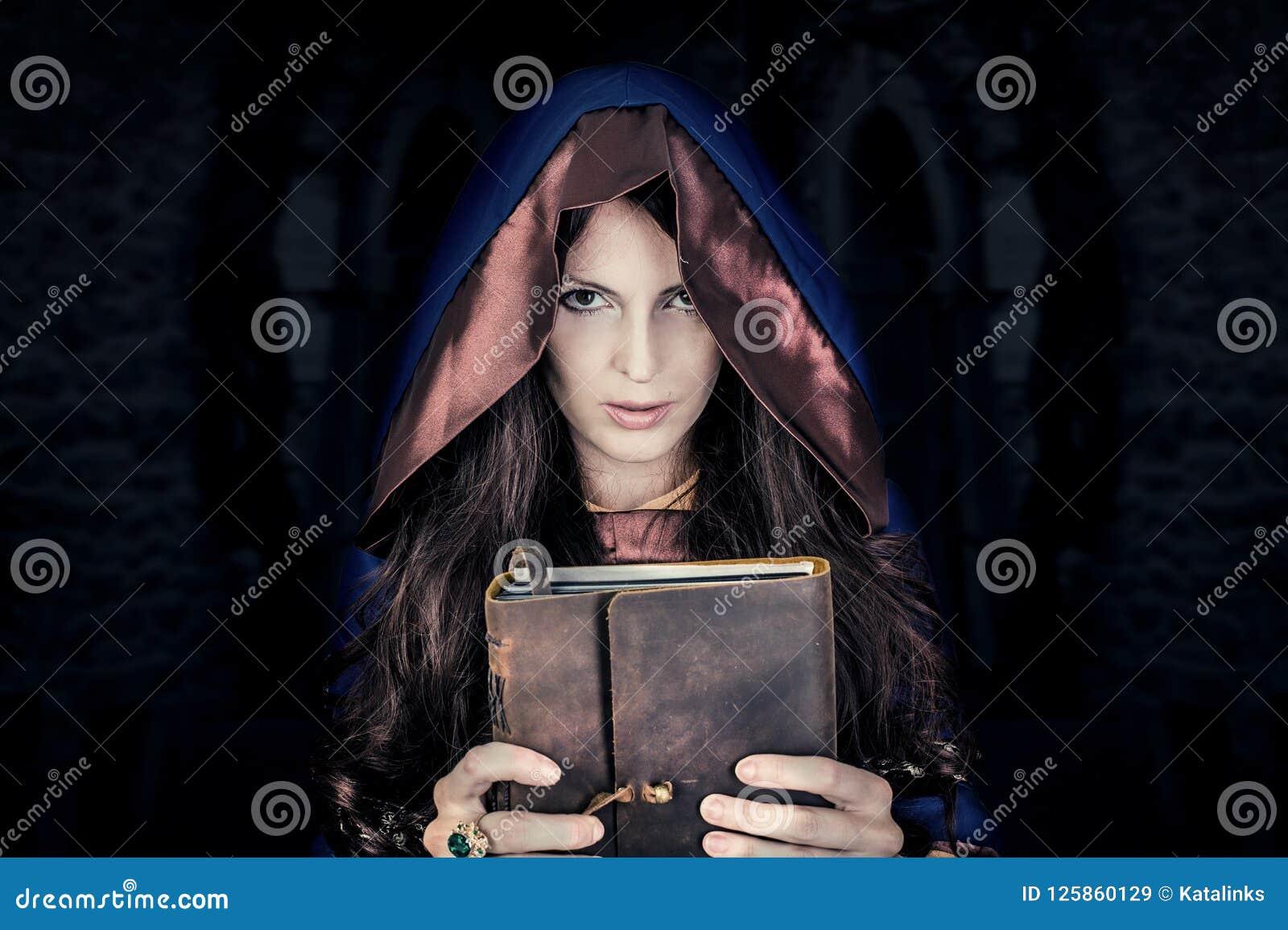 Halloweenowa czarownica trzyma magiczną książkę czary