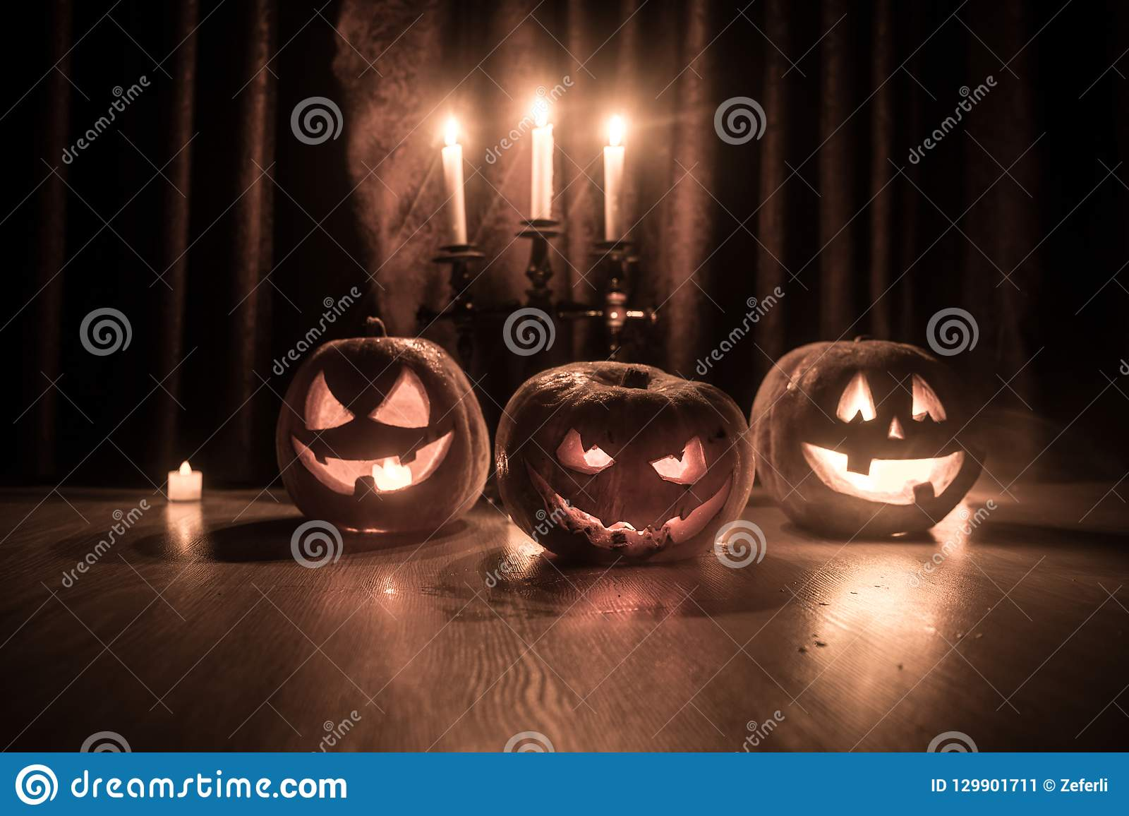 Halloweenowy bani głowy dźwigarki o lampion z rozjarzonymi świeczkami na tle Banie na drewnianej podłoga