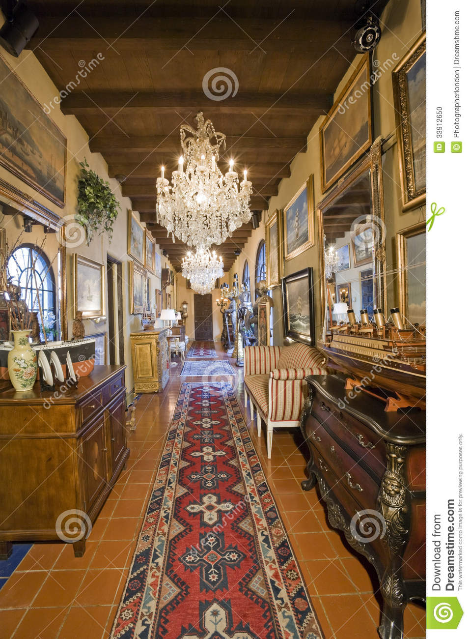 Hallway With Frames And Hanging Chandelier Stock Photo