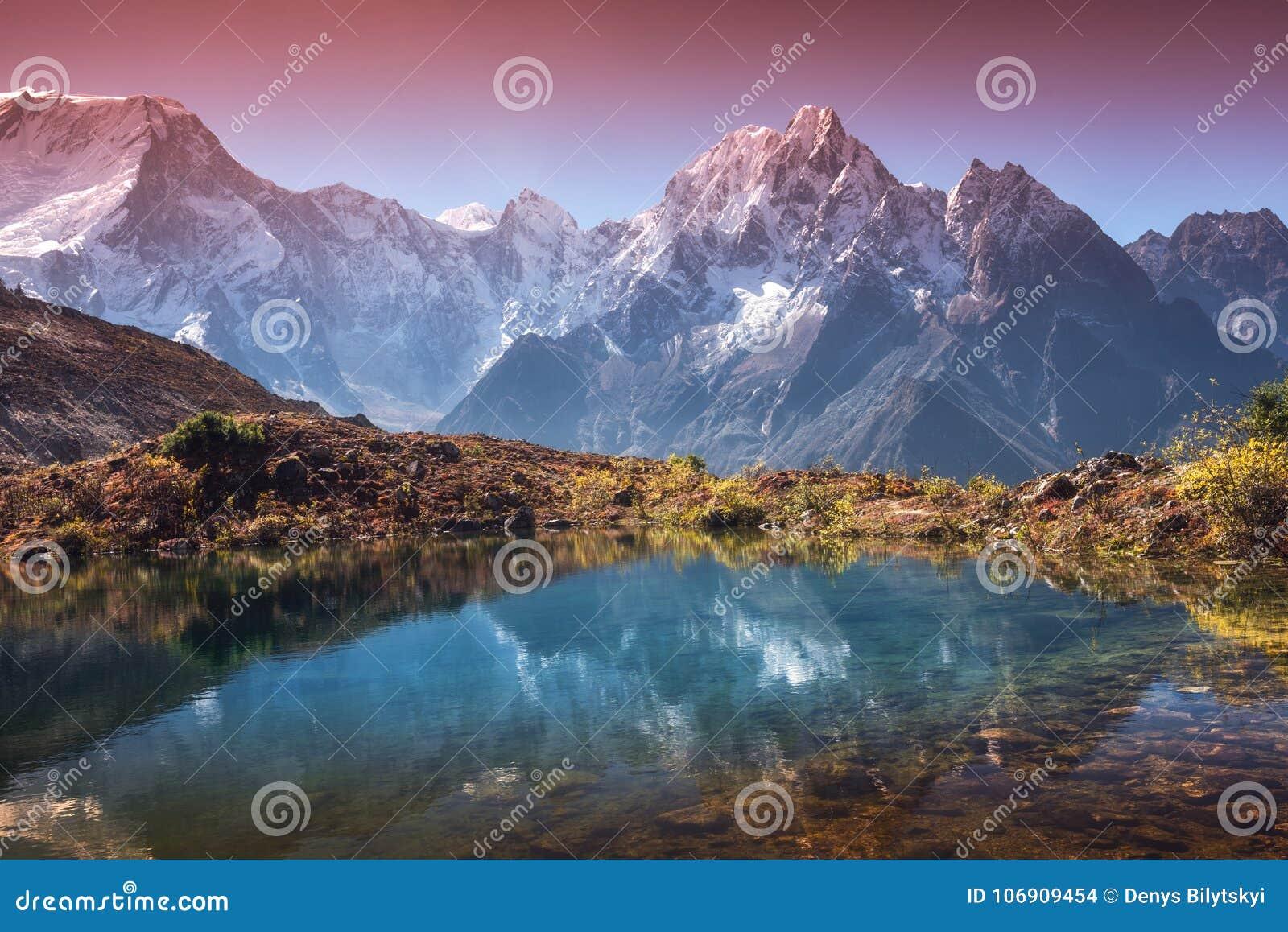 Halna dolina z odbiciem w wodzie w wschodzie słońca