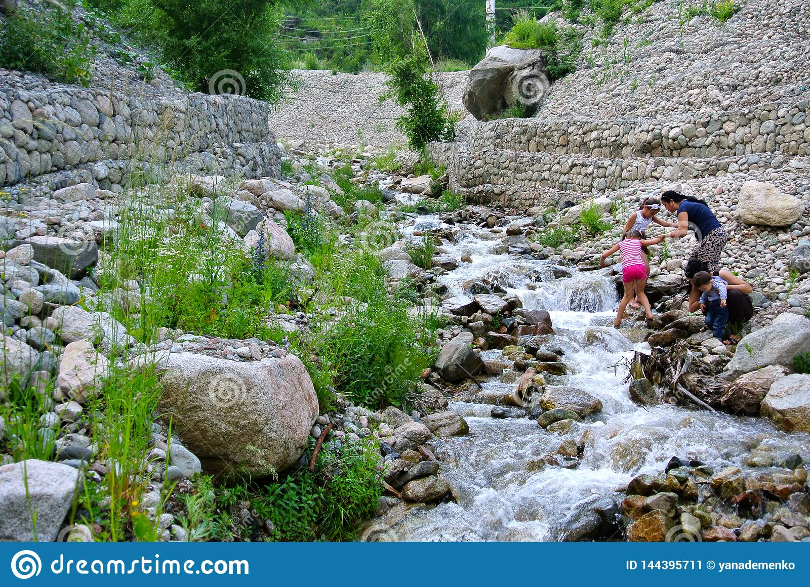 Halny strumień i dwa Azjatyckiej kobiety z ich dziećmi na skalistym brzeg kazakhstan